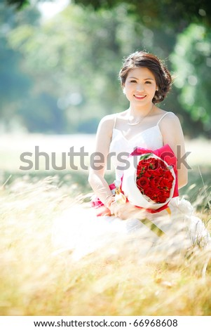 a bride holding a bouquet of rose in the dry field - stock photo