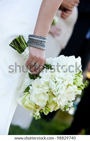 a bride holding a green and white wedding bouquet of flowers