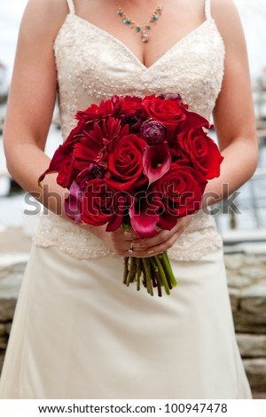 a bride holding her red wedding bouquet of flowers - stock photo