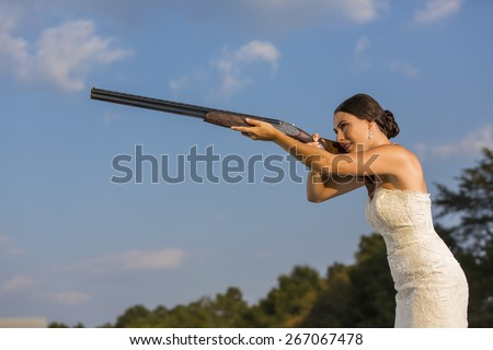 A bride in a wedding dress shooting a shotgun - stock photo
