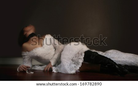a bride on a hardwood floor with moody lighting - stock photo