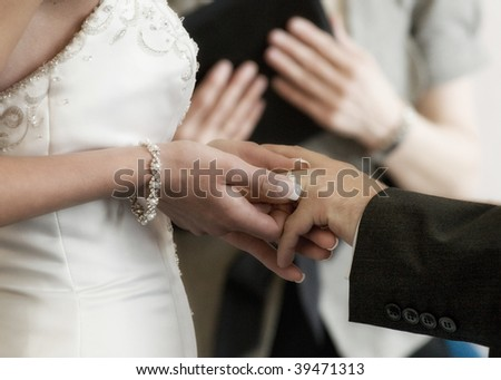 A bride placing a ring on her groom's hand as they get married - stock photo