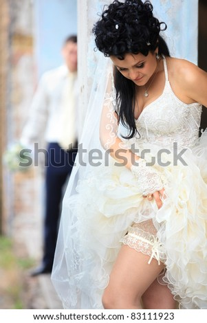 A bride putting on her wedding garter against old grunge place - stock photo