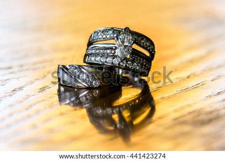 A bride's wedding ring sits atop the ring of her groom.  They are both on yellow wood. - stock photo