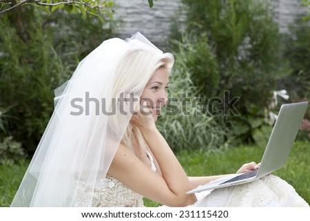 A bride using a laptop - stock photo