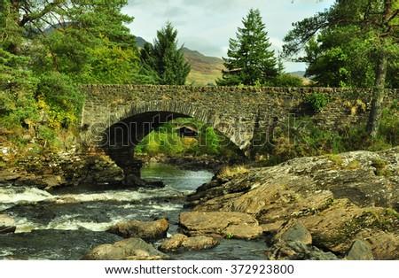 A bridge across the Falls of Dochart, Scotland - stock photo