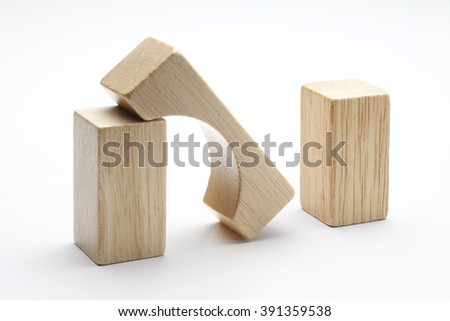 A bridge, built out of small wooden blocks, has collapsed.  Photographed on a white background.