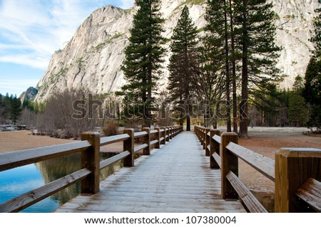 A bridge path lined by trees in Yosemite - stock photo