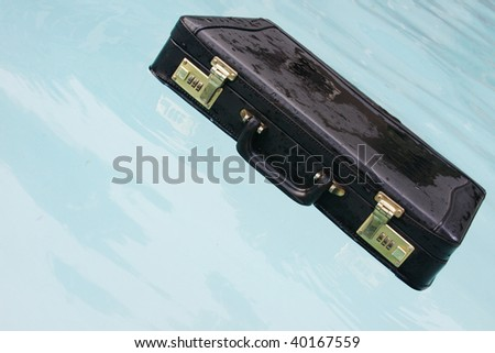 A briefcase floating in the water. - stock photo
