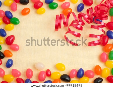 A Bright and Colorful Birthday Invitation Card with Multiple Colors of Jelly Beans and Red Curly Ribbon on Light Yellow Fabric for Texture with Room for Your Wording - stock photo