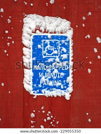 A bright blue handicapped parking sign with snow on sign and siding. - stock photo