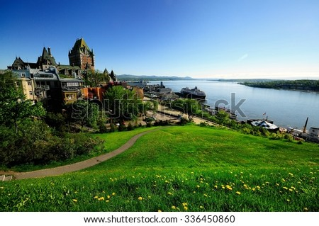 A bright blue morning sky of Vieux Quebec with Chateau Frontenac and St Lawrence River in the background and a green downhill meadow with patches of dandelions in the front.  - stock photo
