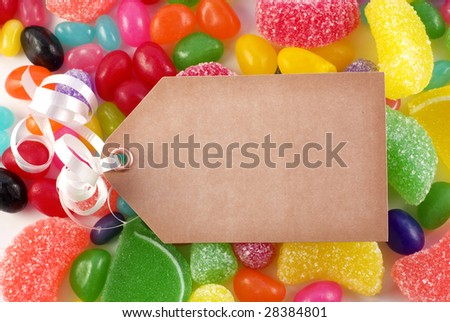 A bright colored assorted candy background with brown tag and ribbon with copy space - stock photo