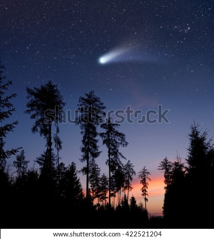 A bright comet is flying in the starry evening sky - stock photo