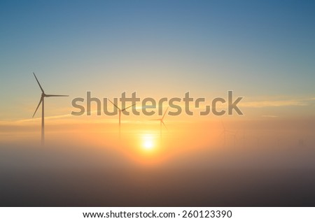 A bright dawn for wind energy: wind turbines generating sustainable energy during a foggy sunrise. - stock photo