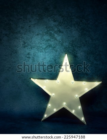 A bright glowing star light is standing on a  textured blue background with text area to add your message. - stock photo