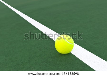 a bright green tennis ball sits on the white line of a green tennis court, diagonal line - stock photo