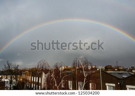 A bright rainbow brightens a grey sky over the the rooftops of London - stock photo