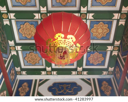 A bright red Chinese lantern hangs from a tiled roof outside a temple in Montreal's Chinatown