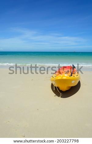 A bright yellow kayak on the beach - stock photo