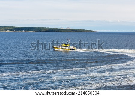 A bright yellow pilot boat speeding across a calm blue harbor