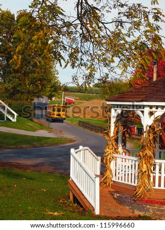 A bright yellow school bus drives along a winding country road on an autumn afternoon. - stock photo