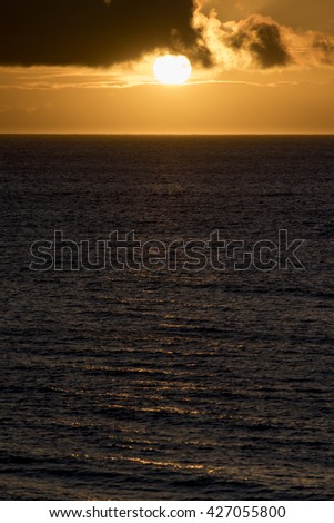 A bright yellow sun setting over the ocean.