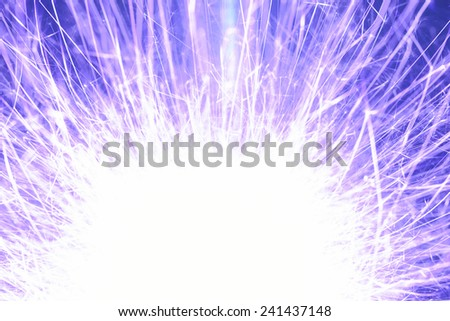 A brightly burning sparkler as a bright background. - stock photo