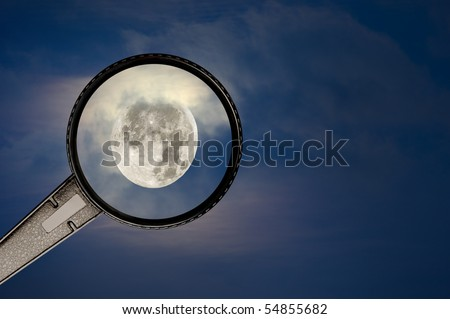 A brightly lit full moon lights up the cloudy, hazy sky while an onlooker uses a magnifying glass to view the moon. - stock photo