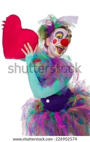 A brightly made up clown holding a red heart in the hands - stock photo