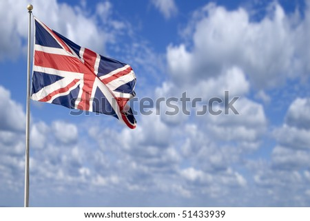 A british flag (The Union Jack) flying in the breeze set against a beautiful summer sky. - stock photo