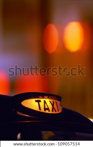 a british london black taxi cab sign at night with colorful background - stock photo