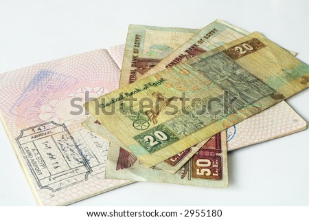 A British passport and Egyptian arrival stamp, together with and assortment of Egyptian pounds. The whole image is in focus (Sheimpflug effect). - stock photo