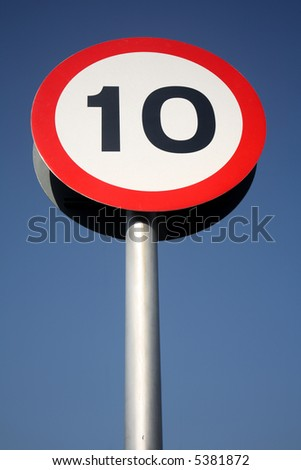A British red and white round 10 miles an hour road sign and a blue sky