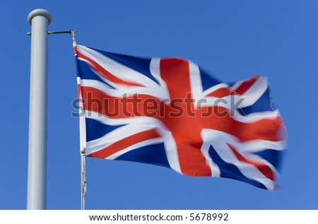 A British Union flag on a flagpole flutters in the wind, this has been shot with a slow shutterspeed to give a sense of movement.