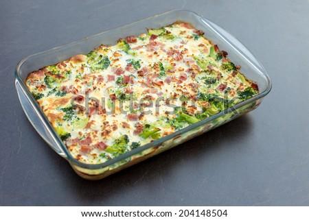A broccoli casserole with ham, egg and feta - stock photo