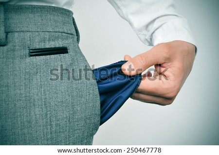 a broke businessman showing his empty pocket - stock photo