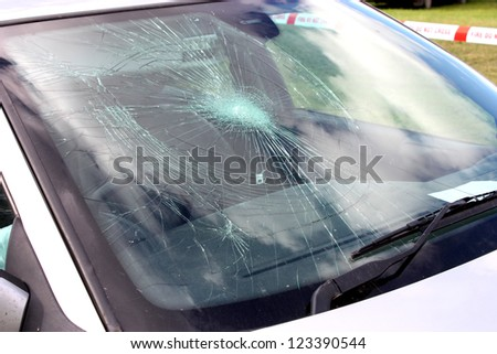 A Broken Car Windscreen at an Accident Site. - stock photo