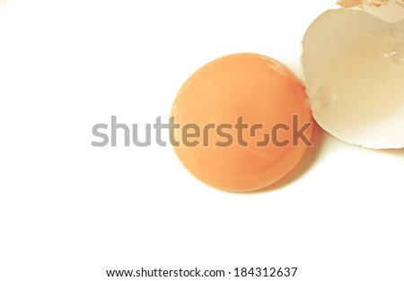 A broken egg and it's yellow yolk