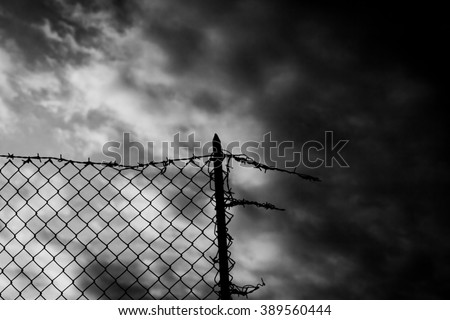 A broken fence over a dark sky. Barbed wire on top. Black-and-white shot. Symbolic shot: escapism, jail, hope, war.  - stock photo