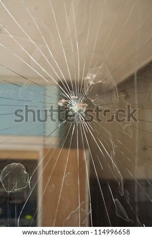 A broken window, with blood left behind as forensic evidence. - stock photo