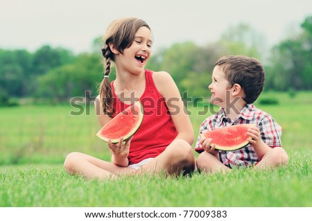 A brother and sister eating watermelon together - stock photo