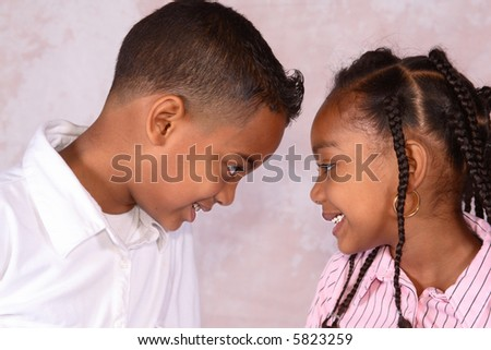 A brother and sister facing each other looking into each others eyes
