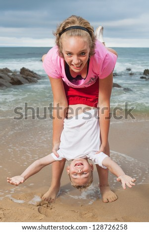 A brother and sister who are playing on the beach. - stock photo