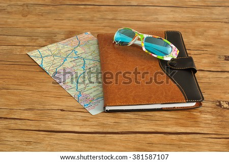 A brown and black leather note book displayed with a copy of a map and sunglasses on a wooden background