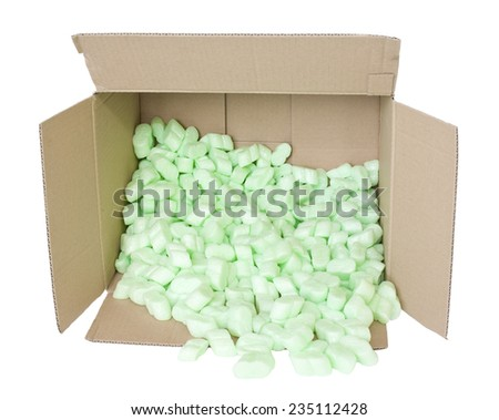 A brown, corrugated cardboard box with green packing foam pellets on a white background - stock photo