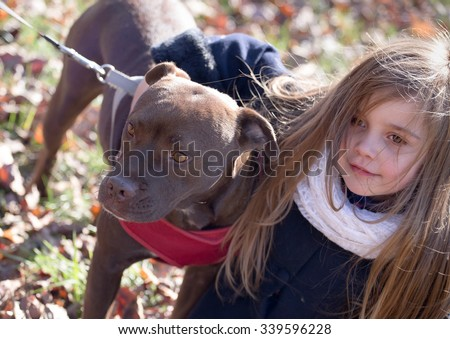 a brown dog on a leash with pink collar being hugged by a little girl on a chilly autumn day, great concept image - children caring for pets - stock photo
