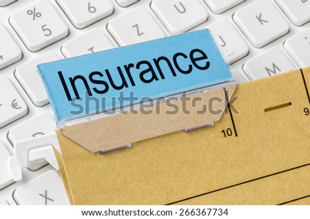 A brown file folder labeled with Insurance - stock photo