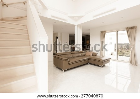 a brown leather sofa at the white living room on the marble bottom, double layered house with stair to second floor.