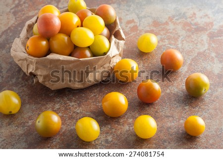 a brown paper bag of fresh picked ripe organic colorful mini tomatoes on textured stone background, top view - stock photo